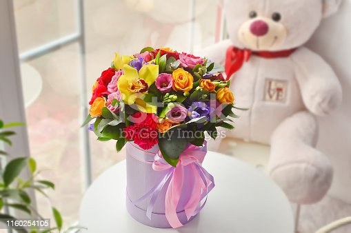 1129427811 istock photo Spring bouquet of flowers in stylish hat box on white table. Beautiful bouquet of colorful flowers in hat box. 1160254105