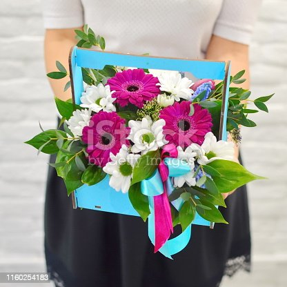 1129427811 istock photo Spring bouquet of flowers in stylish hat box on white table. Beautiful bouquet of colorful flowers in hat box. 1160254183