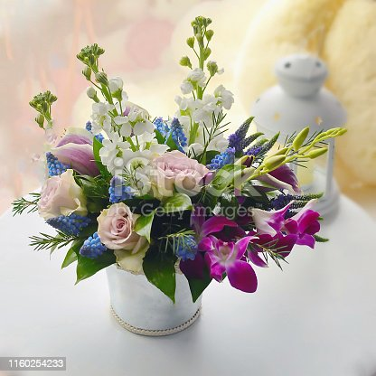 1129427811 istock photo Spring bouquet of flowers in stylish hat box on white table. Beautiful bouquet of colorful flowers in hat box. 1160254233
