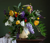 spring bouquet with different garden flowers, lilacs, lupins and tulips, in a can on the table.