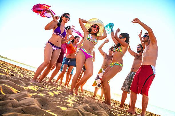 春休みバックライト若者のダンスグループのビーチ ストックフォト