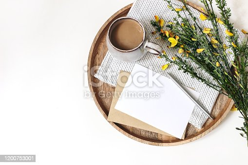 Spring breakfast scene. Yellow broom Cytisus branches, linen napkin, cup of coffee, wooden tray isolated on white table background. Blank greeting card and envelope mockup, Easter flat lay, top view.