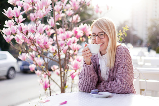 Spring cafe. Young woman drinking coffee at city streets. Attractive happy girl smiling