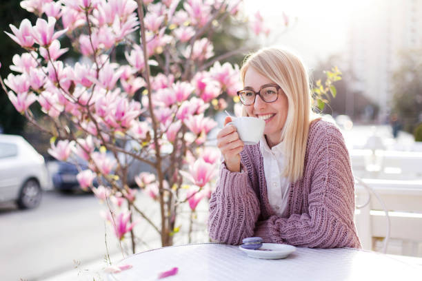 Spring cafe. Young woman drinking coffee at city streets. Attractive happy girl smiling stock photo