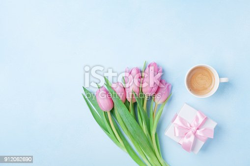 istock Spring card for Woman or Mothers Day. Gift box, tulip flowers and cup of coffee on blue pastel table top view. 912062690