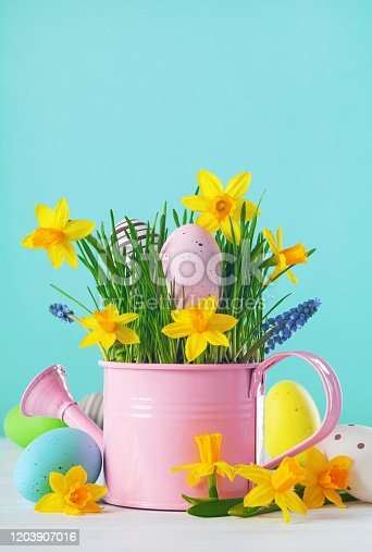 1138213028 istock photo Spring card with colorful Easter eggs, spring daffodil flowers and green grass. 1203907016