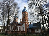 A church sits between some trees in central Latvia