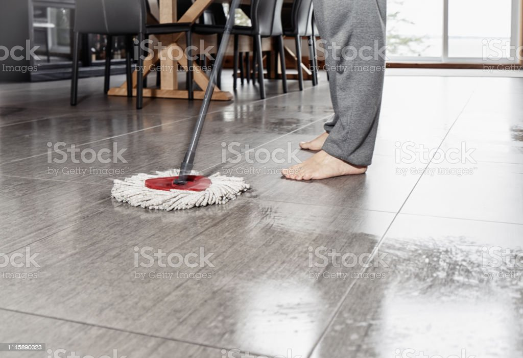 A barefoot man washing his dining room floor with a mop. The mop is...