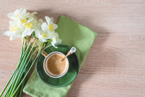 Spring coffee break with bouquet of daffodils