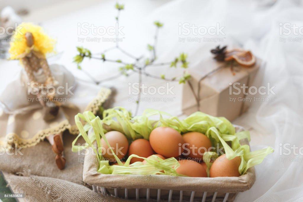 Frühling Komposition. Eine Spielzeugpuppe, Eiern in einen Korb und eine festliche Box mit einem Geschenk – Foto