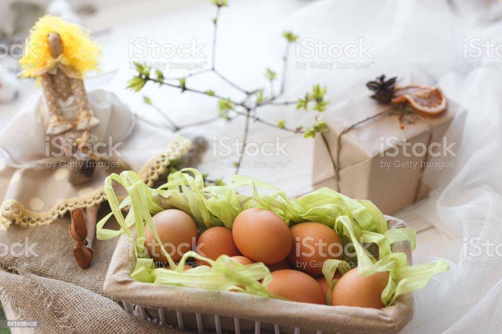 Frühling Komposition. Eine Spielzeugpuppe, Eiern in einen Korb und eine festliche Box mit einem Geschenk. – Foto