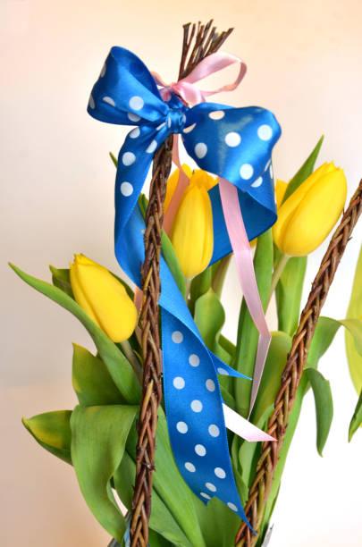 Composición de primavera: dos látigos de Pascua con un montón de tulipanes amarillos - foto de stock