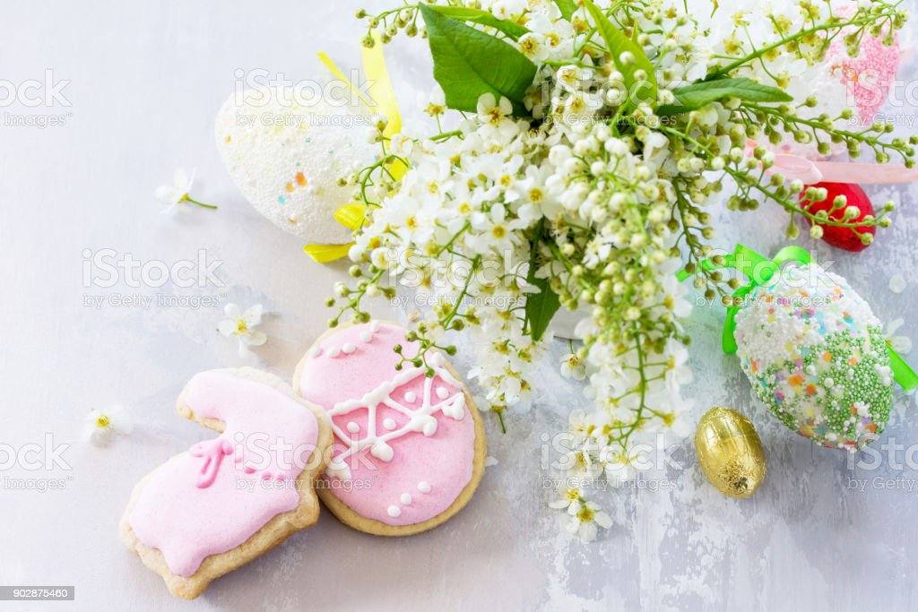 Spring concept. Colorful Easter background with colored eggs and Easter baking on a gray stone background with copy space. stock photo