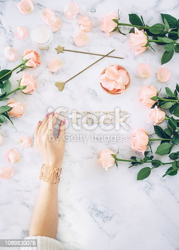 Spring concept flat lay: female hand holding a wooden letter among rose petals on a marble background