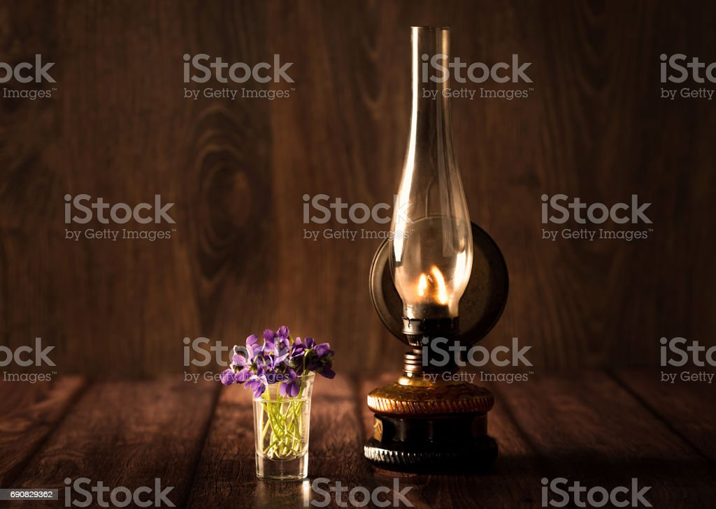 Spring concept with violet and oil lamp on wooden table stock photo