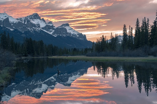 Scenic Sunset Evening Colors at Canmore Spring Creek Mountain Village and Distant Snowy Rocky Mountain Peaks Landscape in early Springtime, Alberta Canada