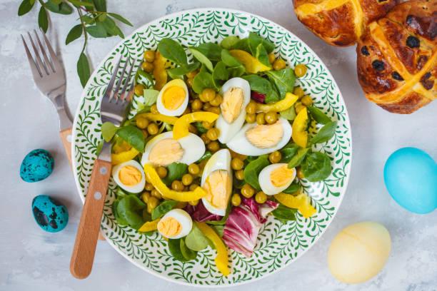 frühling ostern salat mit huhn und wachteleier, cross-brötchen, eiern gemalt. ansicht von oben, raum zu kopieren. ostern-konzept. - englischer erbsen salat stock-fotos und bilder