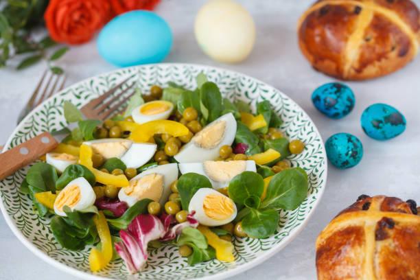 frühling ostern salat mit huhn und wachteleier, cross-brötchen, eiern gemalt.  ostern-konzept. - englischer erbsen salat stock-fotos und bilder
