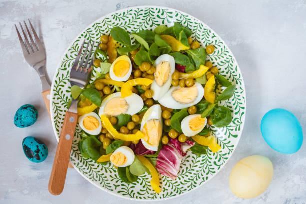 frühling ostern salat mit huhn und wachteleier, kopfsalat, mais, pfeffer, bemalten eiern. ansicht von oben, raum zu kopieren. ostern-konzept. - englischer erbsen salat stock-fotos und bilder