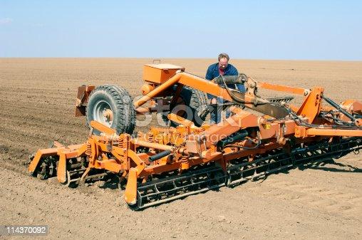 Cultivator prepares spring field for seeding. Farmer adjusts the machine.