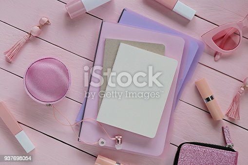 istock spring flat lay in rose tone. Blank Notepad and lipstick, headphone,rose glasses, earrings, handbag on a pink wooden plank background. flat lay with fashion accessories in pastel pink tones.Top view 937698054