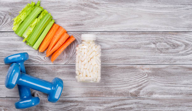 Spring flatlay sports composition with celery an carrots blue dumbbells ant l-carnitin vitamins in capsules on gray wooden background. Concept healthy lifestyle, sport and diet in spring. Top view. stock photo
