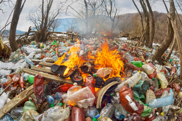 Spring flood and shore with garbage Tourist photographed a panorama of ecological disaster - the river carries plastic rubbish to Europe, abandoned by non-cultural populations. plastic fire releases dangerous chemicals plastic pollution stock pictures, royalty-free photos & images
