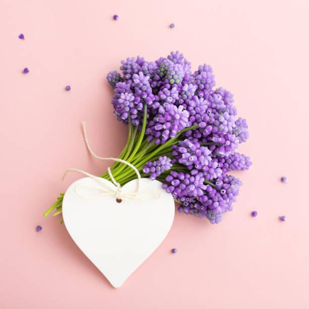 Frühlingsblumen und ein Herzstück markieren Mockup auf rosa für den Muttertag. – Foto
