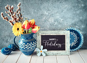 Spring flowers in classic blue color ceramic pitcher with matching plate, spring flowers, Easter eggs with polka dots and a blackboard. Text \