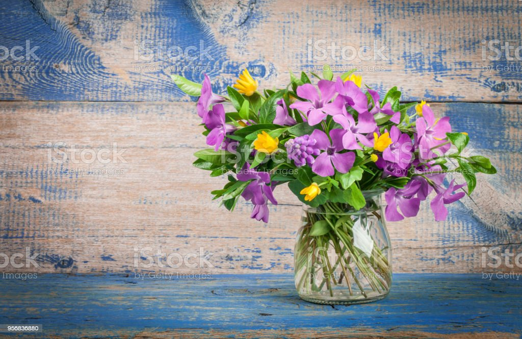 Spring Flowers In Glass Vase On The Background Of Old Wooden Boards