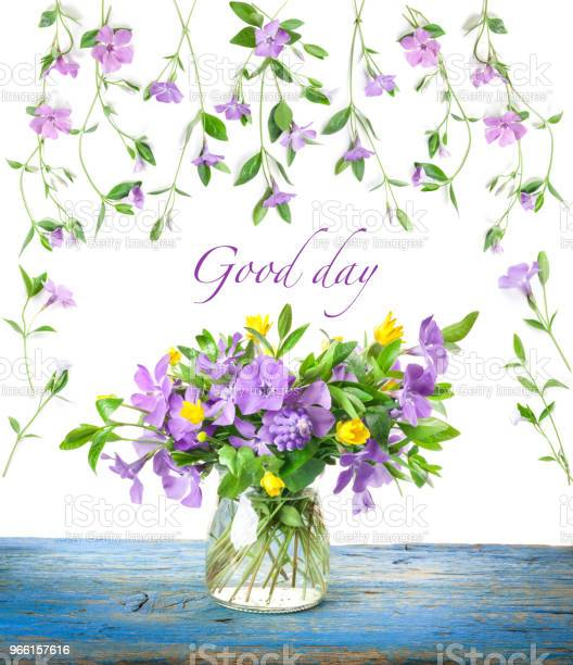 Spring Flowers Periwinkle In Glass Vase On Old Wooden Board Stock Photo - Download Image Now