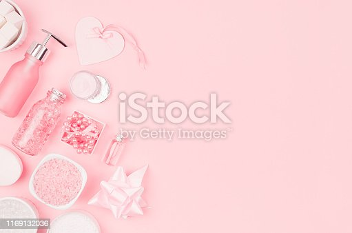 istock Spring fresh cosmetic products for makeup and bath in pastel pink color as decorative border, top view. 1169132036