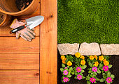 A aerial view of a red wood deck with clay flower pots, work gloves, and spade.  The aerial shot alto shows the perfectly cut yard with stone pavers and flower bed.  Please see my portfolio for other gardening related images.