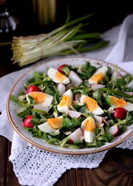frühgrüner salat aus bio-radieschen, wilder knoblauch mit gekochten eiern, olivenöl und parmesan. - bärlauchsalz stock-fotos und bilder