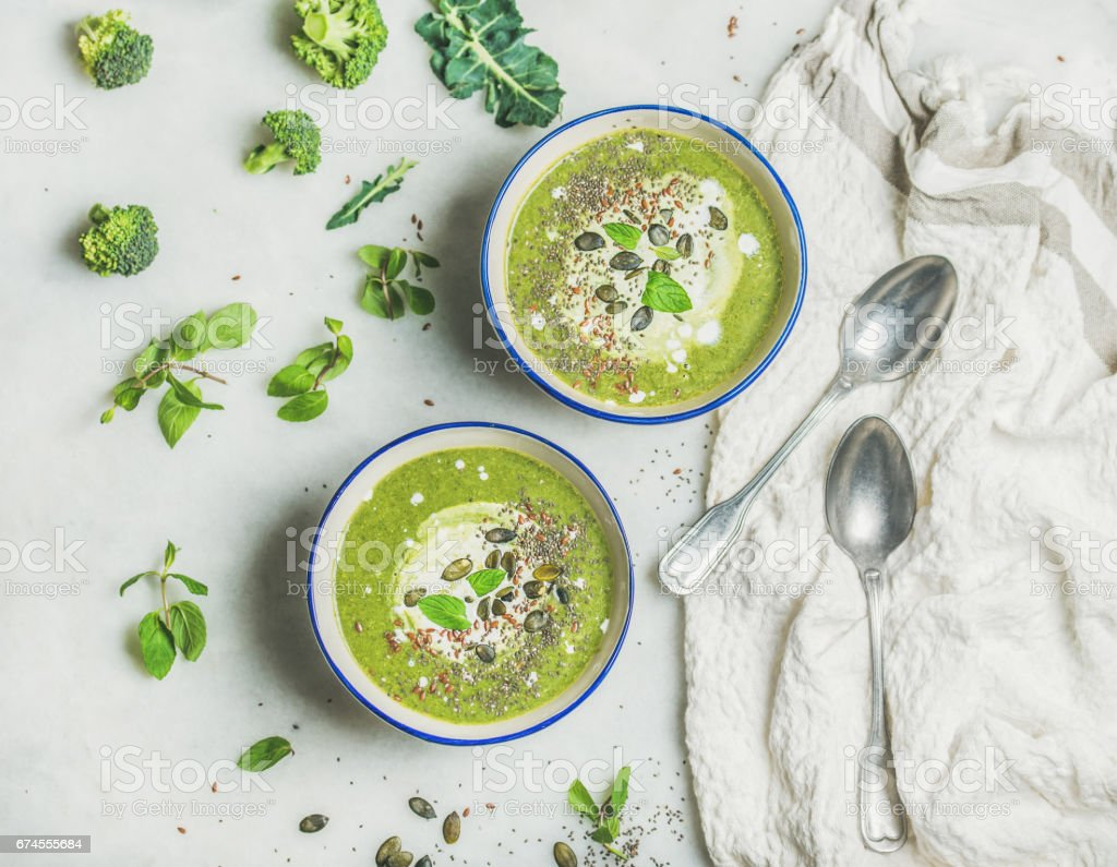 Spring healthy broccoli cream soup with mint and coconut cream stock photo