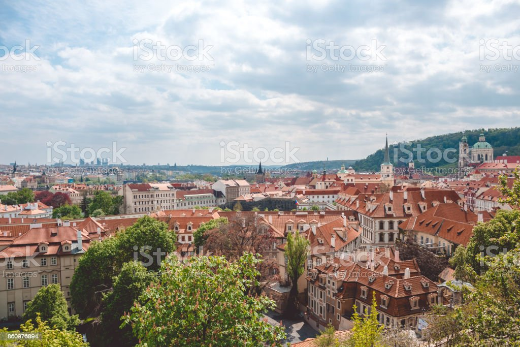 Spring in Prague. Old houses with a red tile roof and bright green foliage. Historical Quarter stock photo