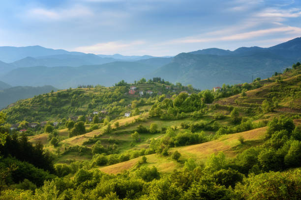Spring is coming... Amazing spring view with a little village in Rhodopi Mountains, Bulgaria. Magnificent landscape, green fields, small houses - Image stock photo