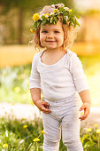 Cute Caucasian toddler girl is playing in the front yard on a beautiful spring day. She is wearing a wreath made of fresh wildflowers.