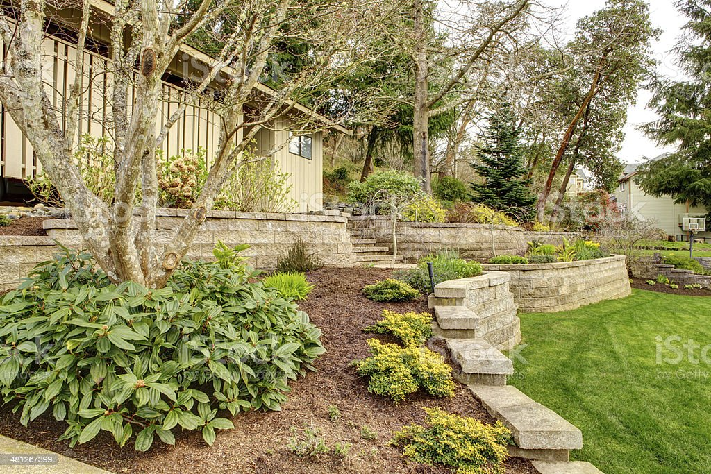 Spring Landscape with retaining walls and garage. stock photo