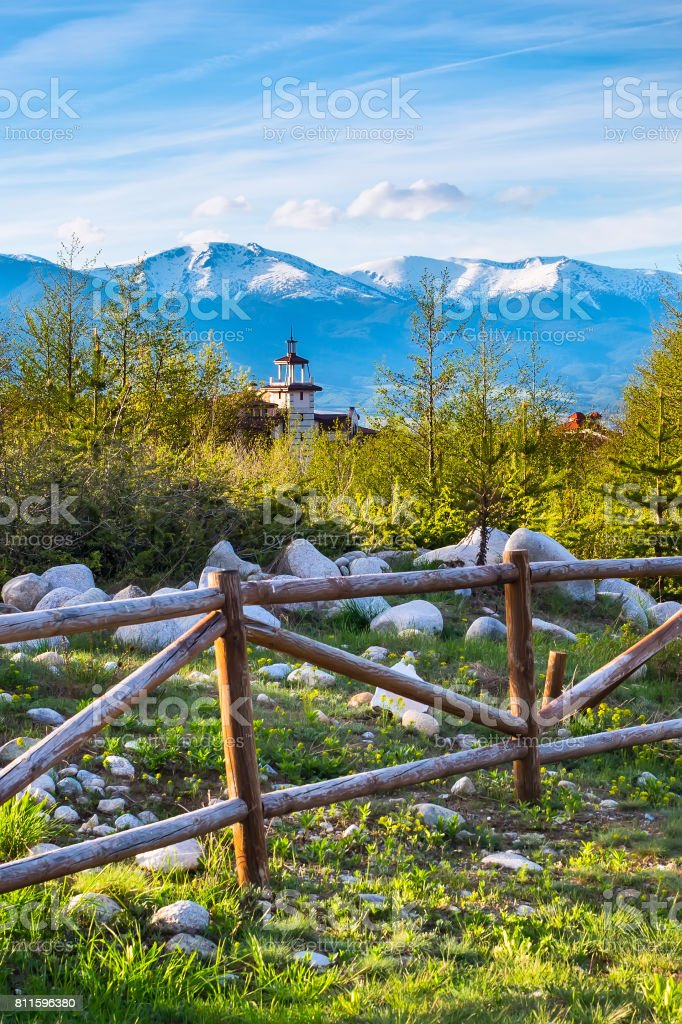 Spring landscape with wooden fence, trees, snowy mountain peaks stock photo