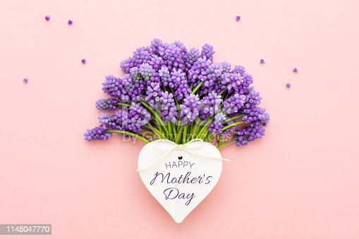 Spring lilac flowers and a heart shape card with text Happy Mother's Day over pink background. Flat lay.
