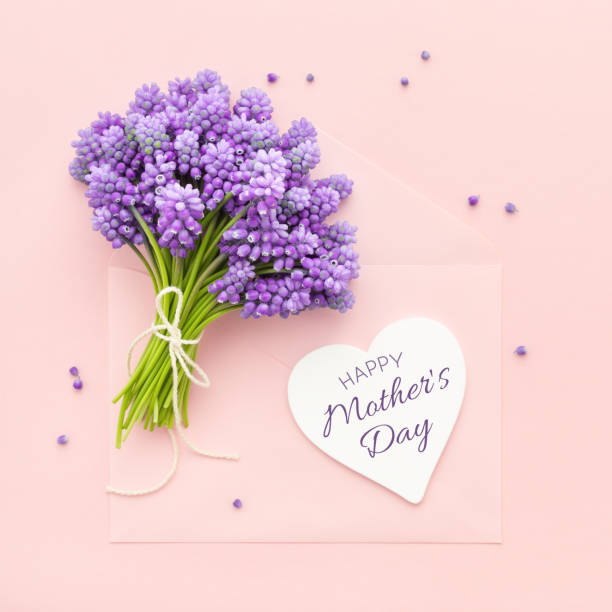 Frühlingslila Blumen und eine Herzform Karte Happy Mother es Day auf rosa Umschlag. – Foto