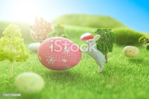 Spring meadow with a two white rabbit and easter eggs. Fairy tale