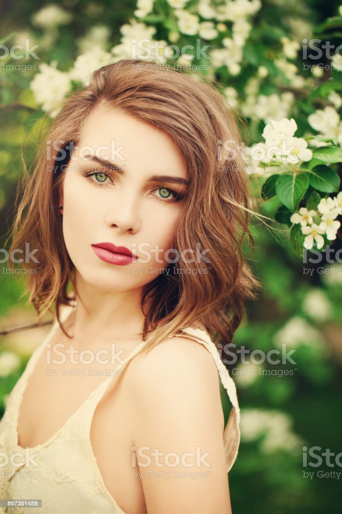 Spring Model Woman with Long Bob Hairstyle. Sexy Beautiful Girl with Healthy and Beauty Brown Hair on Spring Blossoms Background stock photo