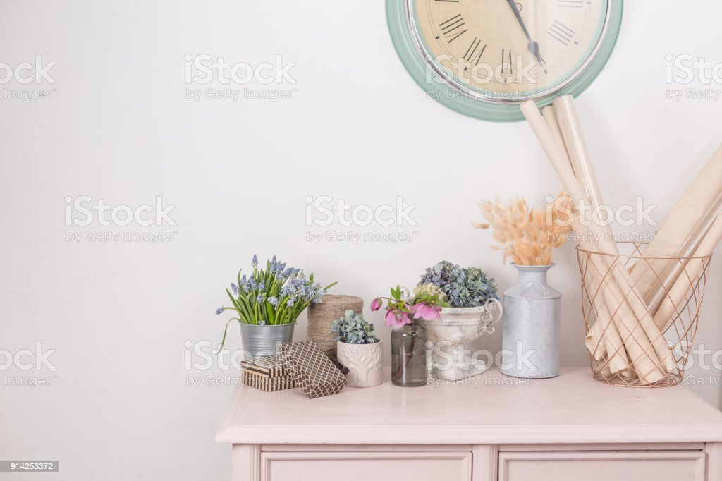 Frühlingsstimmung. Vintage Inneneinrichtung. Rosa Pastell Schrank. Trockene und frische Blumen auf Holztisch. Eine große Uhr auf einer weißen Wand. Textfreiraum – Foto
