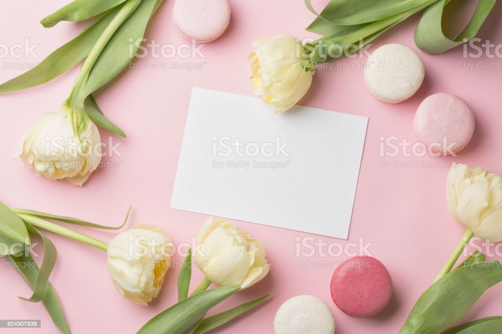 Spring morning concept flatlay of white flowers card and macarons flat lay of white flowers card and macarons over light mightylinksfo