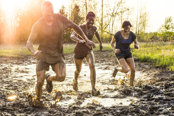 Spring Mud Run Three young adults are testing their agility and endurance during an extreme challenge of running through mud outdoors. Here, the sunset is behind them as they race through muddy water. mud run stock pictures, royalty-free photos & images