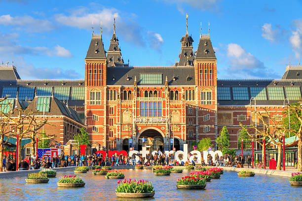 Spring Museum Amsterdam, The Netherlands - May 2, 2014: Beautiful vibrant spring view of tourists at the Rijksmuseum in Amsterdam on May 2, 2014 museumplein stock pictures, royalty-free photos & images