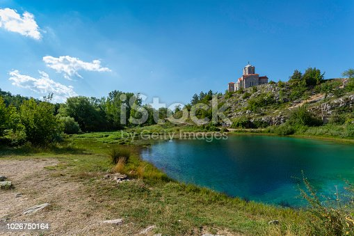 Spring of Cetina river in Dalmatia, very deep and dark blue hole with cold water, rocky and green bushes surrounding the lake and almost clear blue sky
