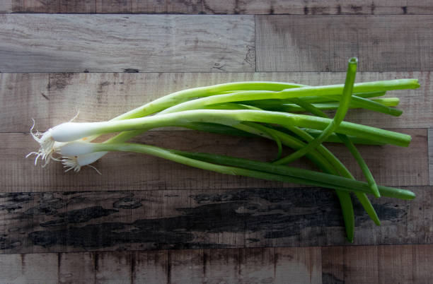 Spring onions on wooden table stock photo